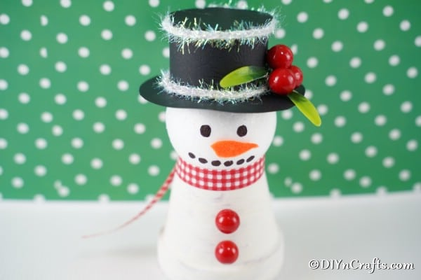 Snowman decoration in front of green polka dot background
