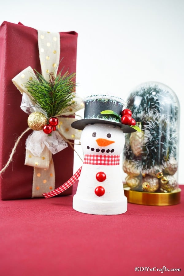 Up close picture of clay pot snowman decor on a red tablecloth