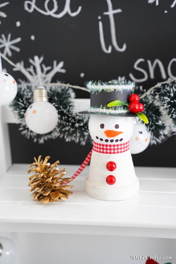 Clay pot snowman decoration on a white shelf in front of chalkboard let it snow sign