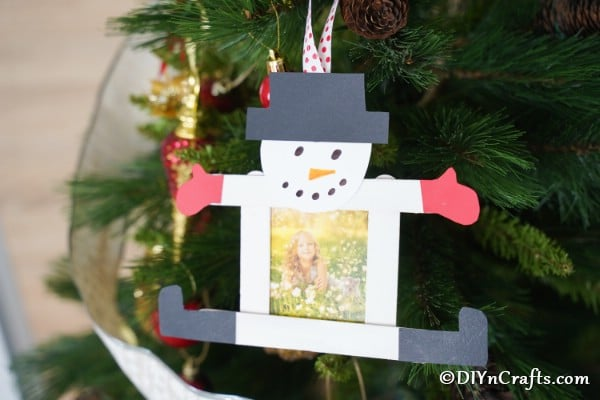 A snowman craft stick ornament hanging on a cedar Christmas tree