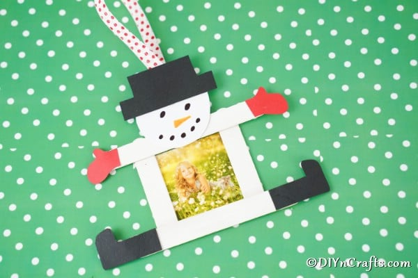 A craft stick snowman ornament laying on green and white polka dot surface