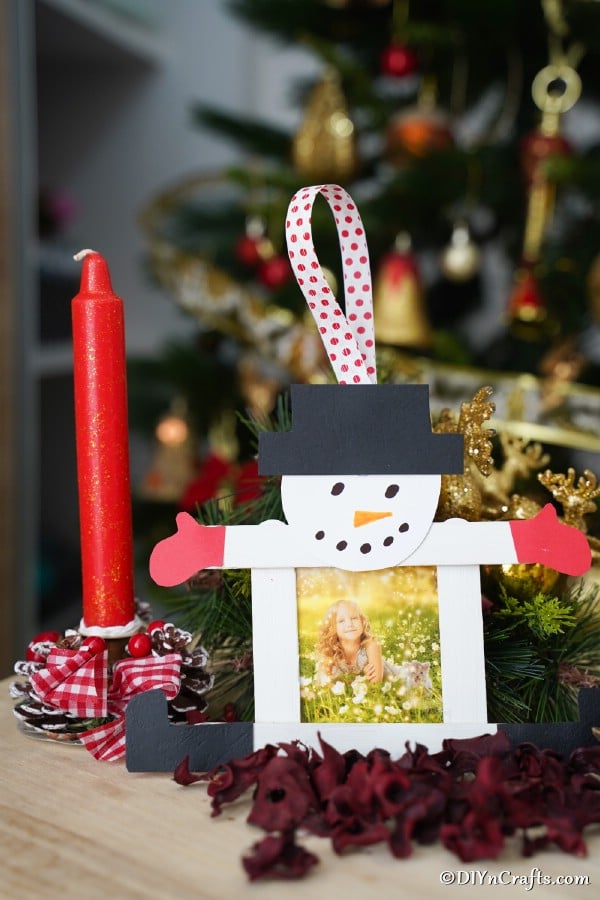 A snowman craft stick picture ornament sitting on a table next to holiday candles and wreaths