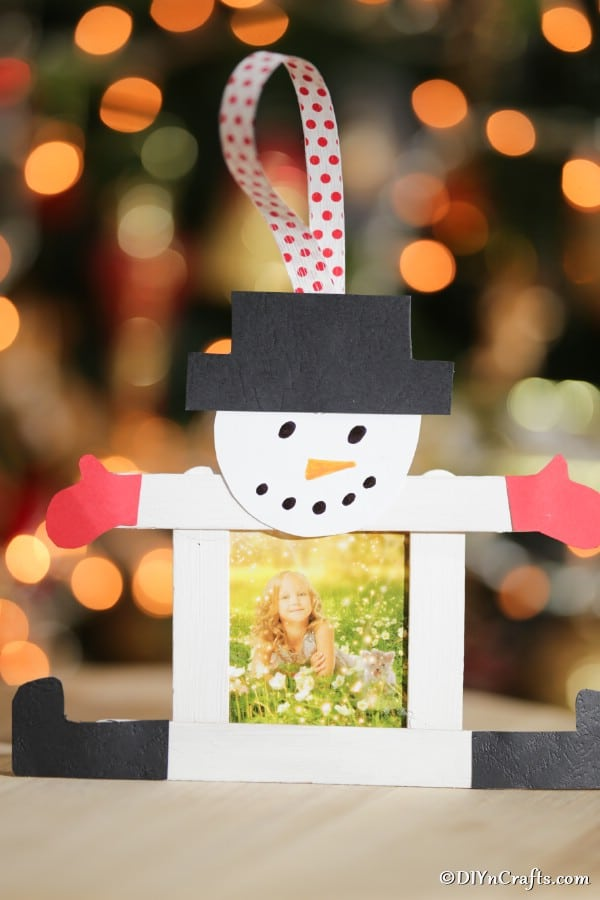 A completed craft stick snowman picture frame in front of a holiday tree
