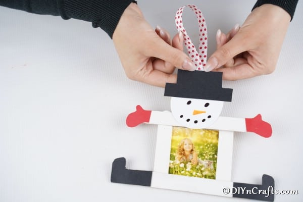 Attaching the ribbon to your craft sticks snowman photo ornament