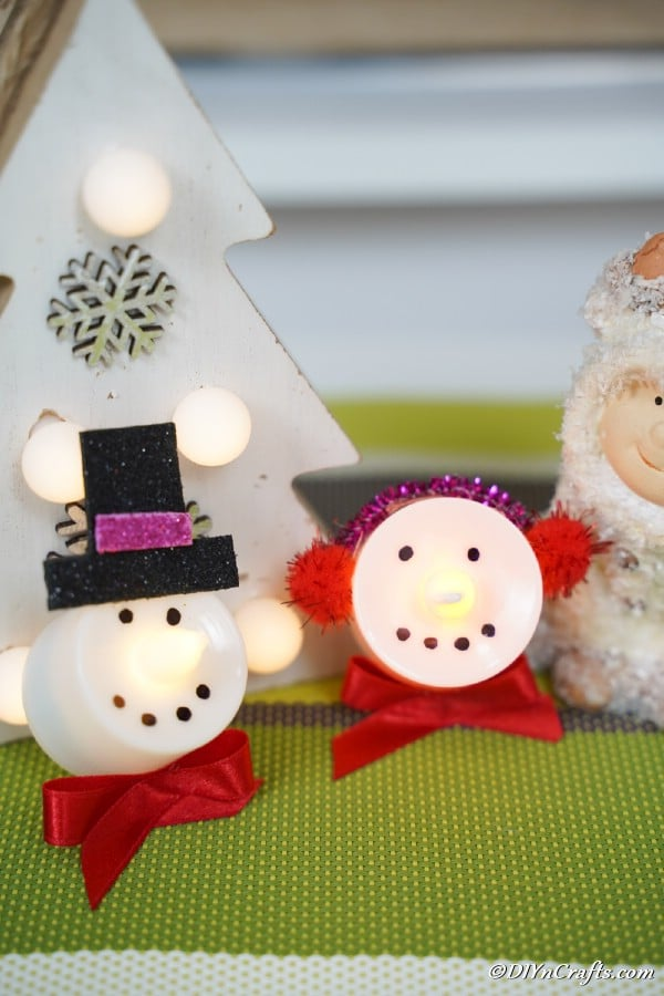 Snowman and Santa Christmas candles displayed on a green table