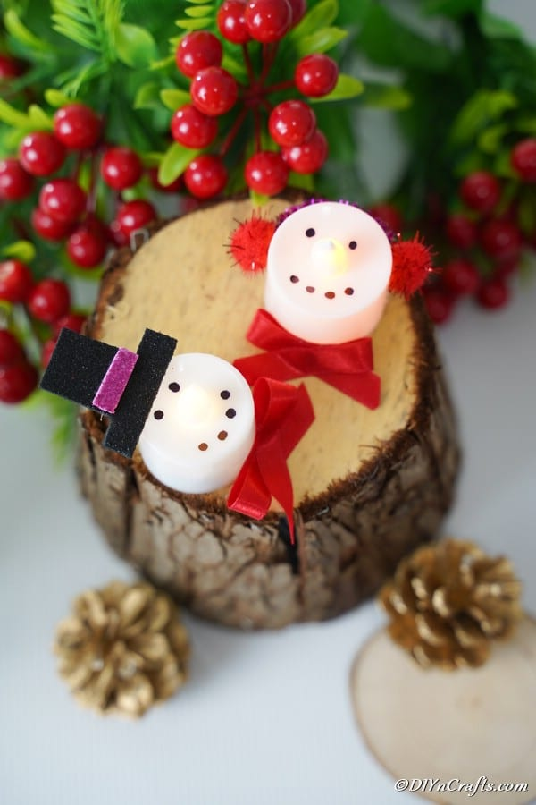 Snowman and Santa candles sitting on top of a slice of wood with holiday decorations around them