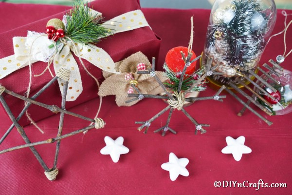 Rustic twig ornaments displayed ona maroon tablecloth