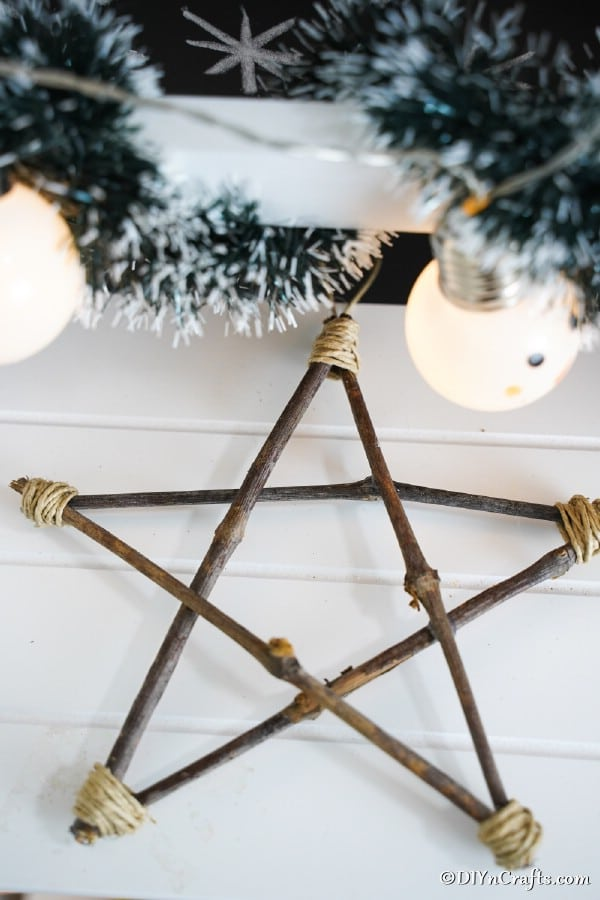 A rustic Christmas ornament star laying on a wooden table