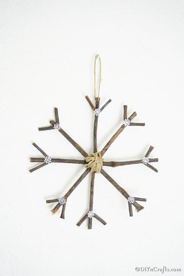 A snowflake rustic Christmas ornament hanging on a white wall