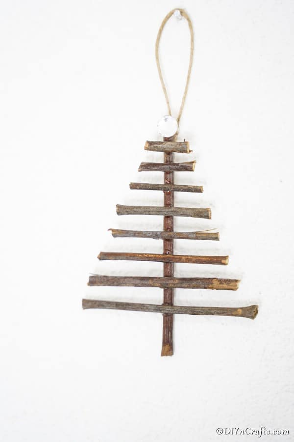 A tree shaped rustic Christmas tree ornament hanging on a white wall