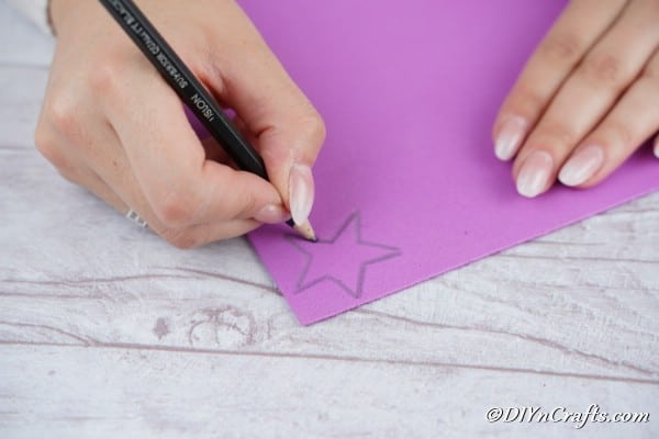 Drawing a straw onto the glitter paper to attach to the tree