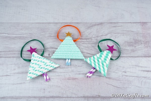 Three paper Christmas tree crafts on a wooden surface