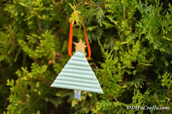 A paper Christmas tree hanging in a cedar tree