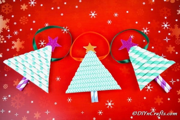 Paper Christmas tree craft ornaments laying on a red surface with holiday theme