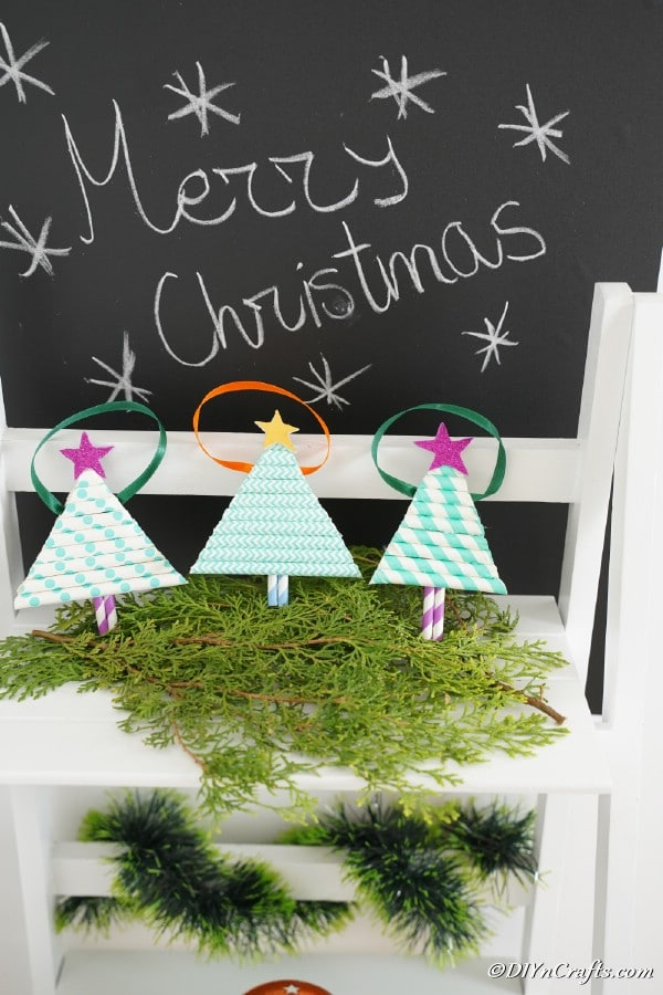 Paper Christmas tree ornaments displayed on a shelf with holiday greenery
