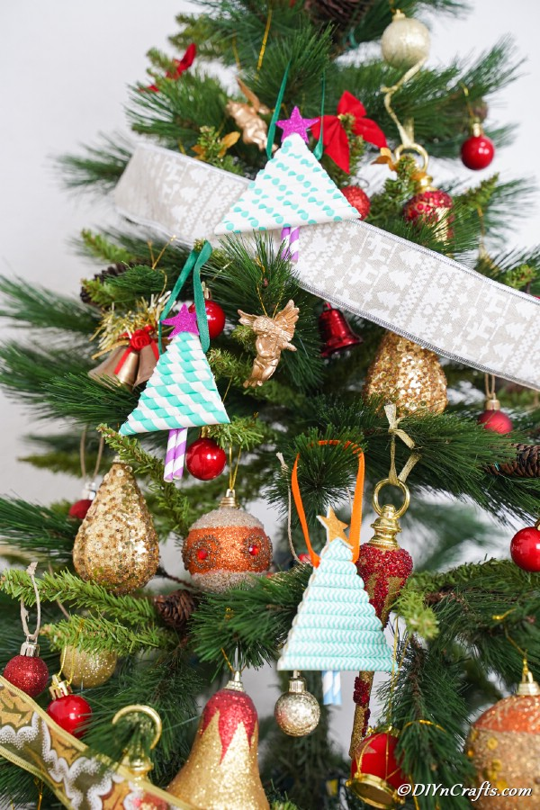A Christmas tree with paper Christmas tree ornaments hanging on it with ribbon