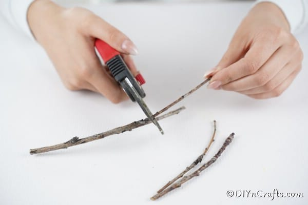 Trimming twigs to make holiday ornaments