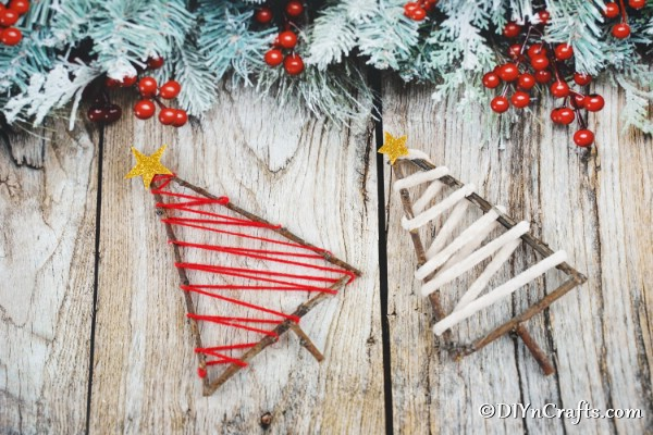 Two twig rustic ornaments for the holidays laying on a wooden table with holiday decorations