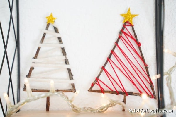 Rustic christmas tree ornaments made from twigs sitting on a white shelf