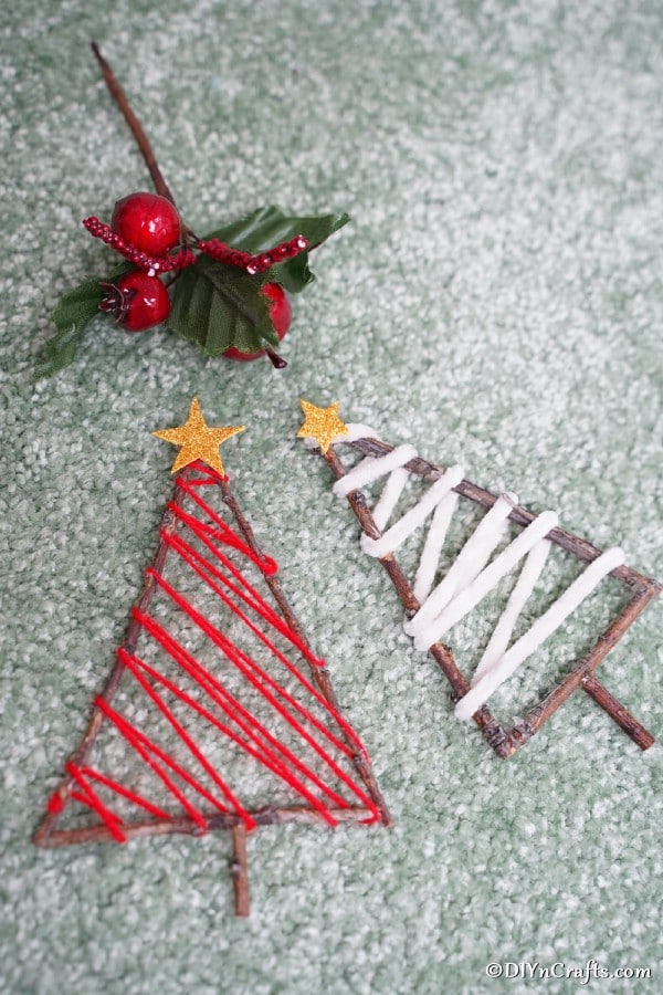 Two twig ornaments laying on a blue surface with a fake holly leaf beside them