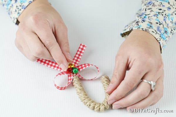 Adding jingle bells to candy cane ornament