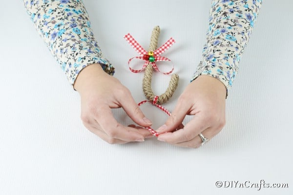 Tying a ribbon on the top of an ornament