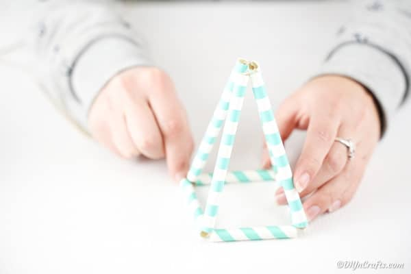 Pulling the paper straws together into a triangle planter shape