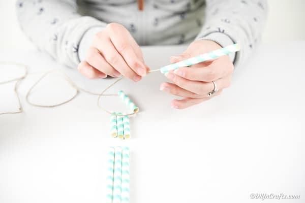 Threading twine into paper straws