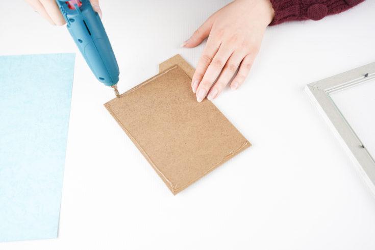Adding hot glue to back of frame