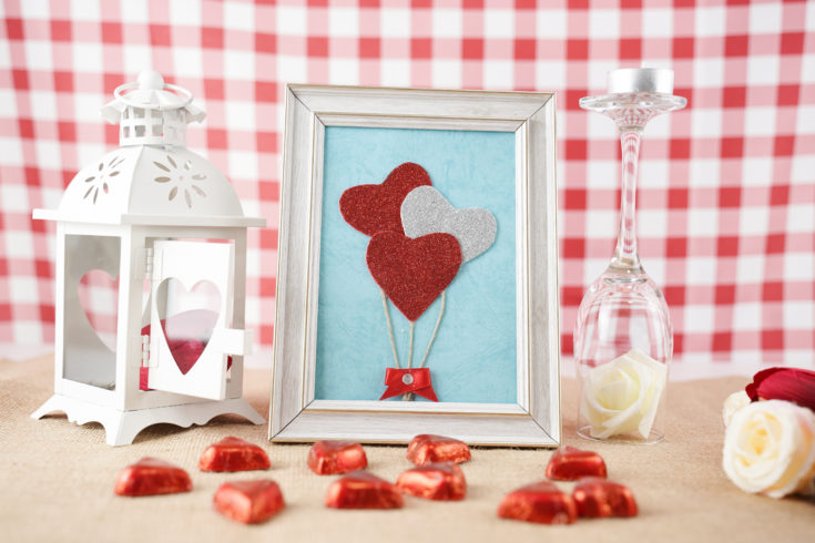 Framed hearts decoration on a wooden table in front of red gingham background
