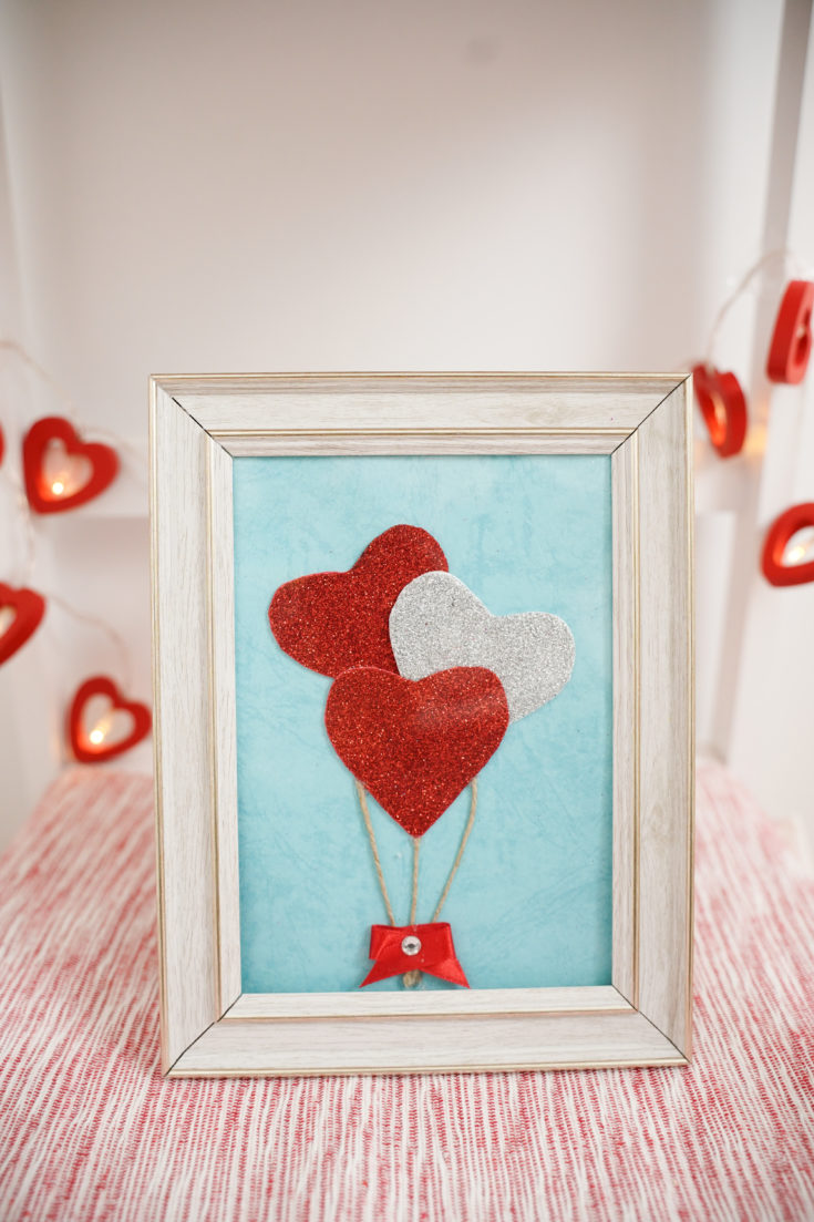 Framed hearts balloons on wooden surface with heart garland behind