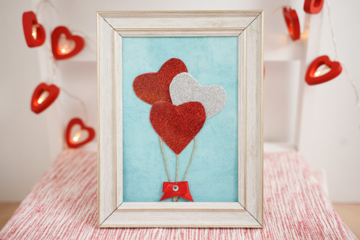 Framed heart balloons decoration on stool with red heart garland in background