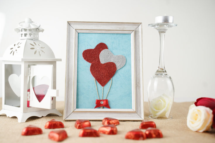 Framed heart balloons on table with Valentine candy