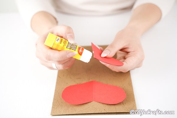 Gluing paper heart to craft paper