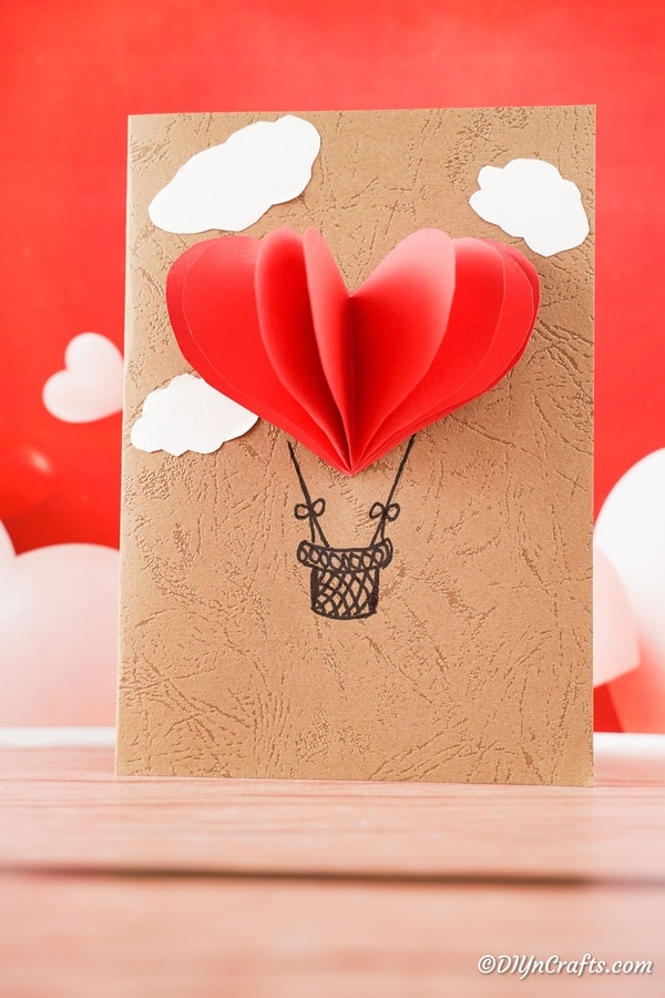 Hot air balloon 3D valentine's day card sitting on table with red background
