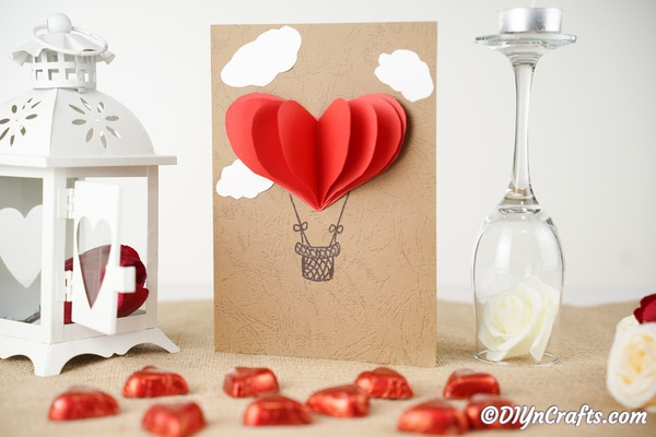 A 3D hot air balloon valentine's day card on table with heart candies