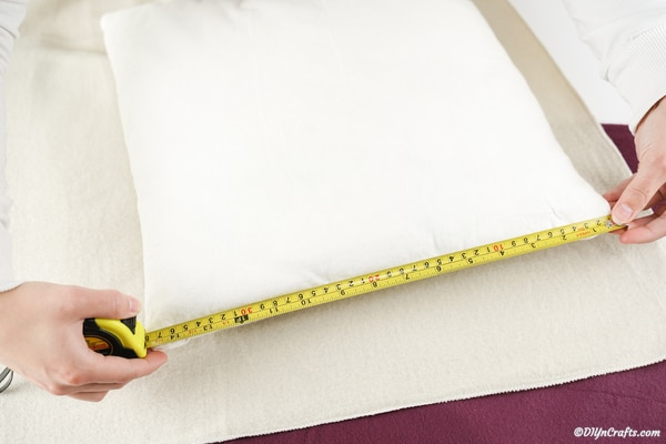 Measuring a throw pillow with ruler