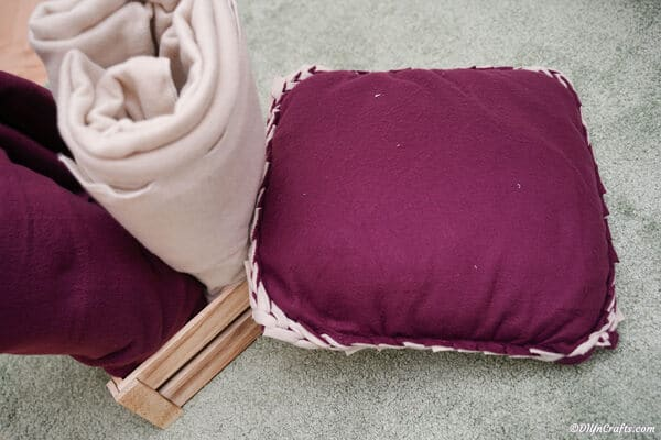 Purple and lavendar no sew pillow on ground