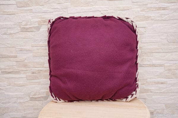 A purple no sew pillow sitting on a wooden stool