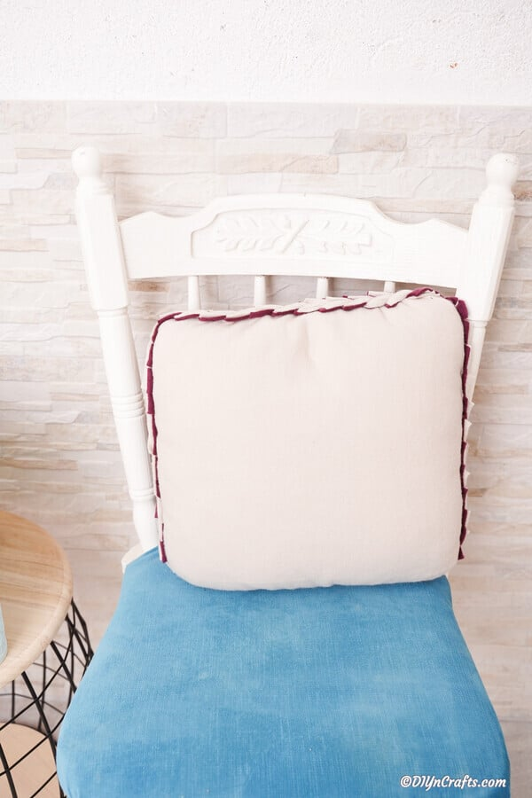 Light purple no sew pillow sitting on white chair with blue cushion