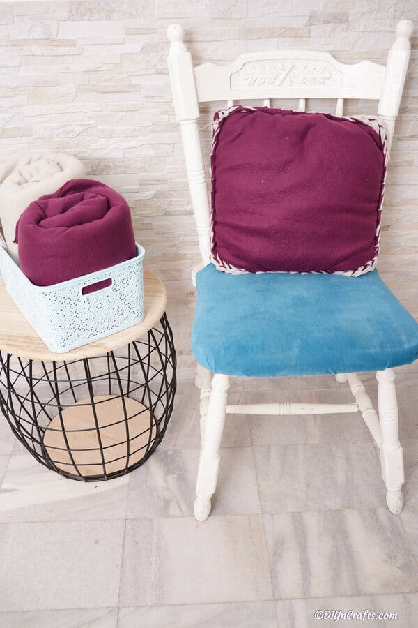 A purple no sew pillow sitting on a white chair