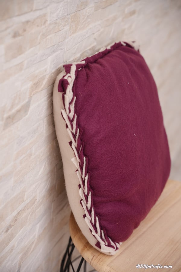 A purple no sew pillowcase leaned against a wall