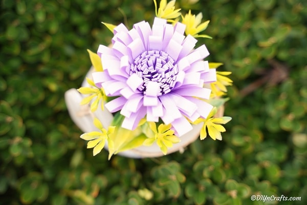 A single paper flower sitting on top of a green shrub