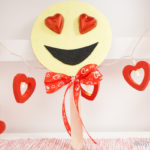 Heart smiley emoji decoration leaned against wall with heart garland