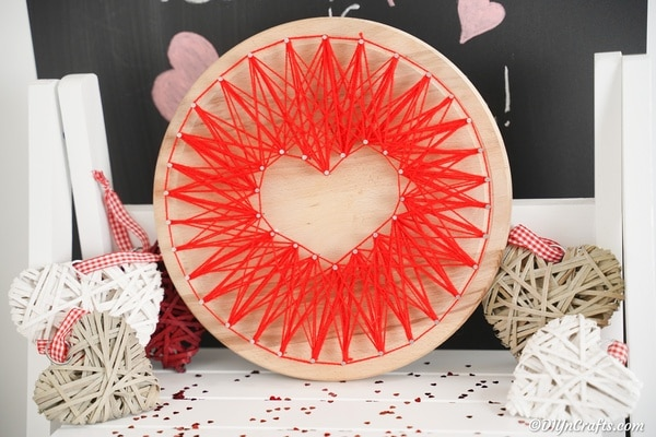 String art heart in front of chalkboard