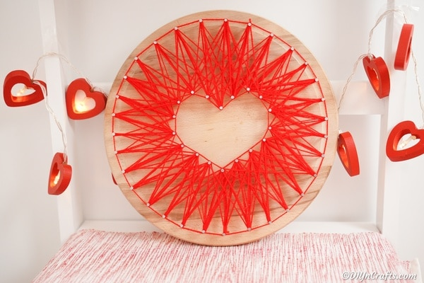 Heart string art in front of white wall with paper heart garland