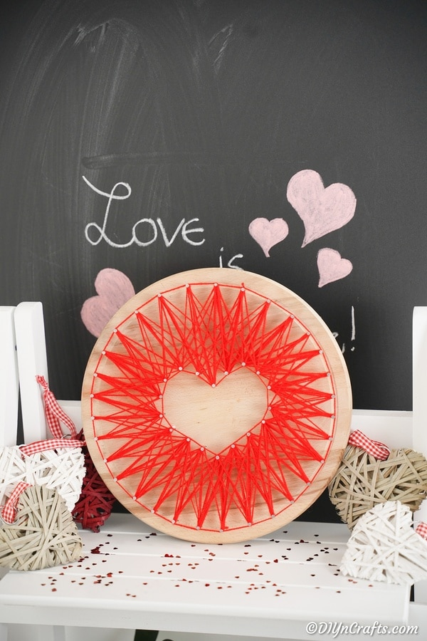 Heart string art leaning against chalkboard