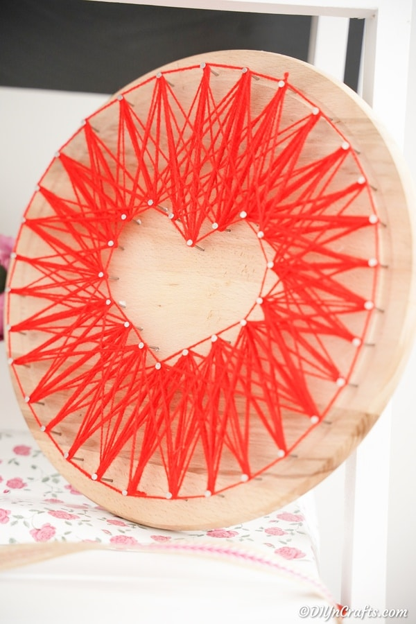 Round wood board with string art in shape of heart