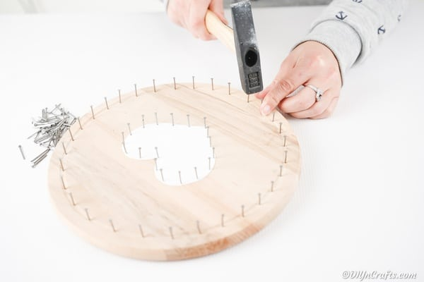 Adding nails to the outer rim of the round wooden board