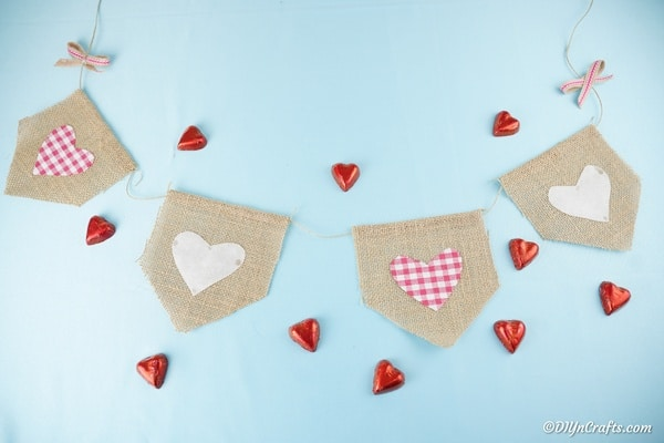 Burlap Valentine's day garland on blue background with red heart candy